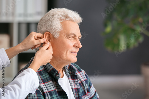 Doctor putting hearing aid in mature man's ear in clinic Canvas