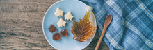 Maple Syrup Bottle And Pure Soft Sugar Candy And Taffy Top View On Kitchen Table Panoramic Banner. Cooking Ngredient For Desssert Recipe, Traditonal Food From Quebec Wood Rustic Plate Panorama.