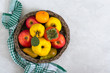 Fruit basket on a light concrete background. Seasonal fruits are a source of vitamins and health. Copy space.