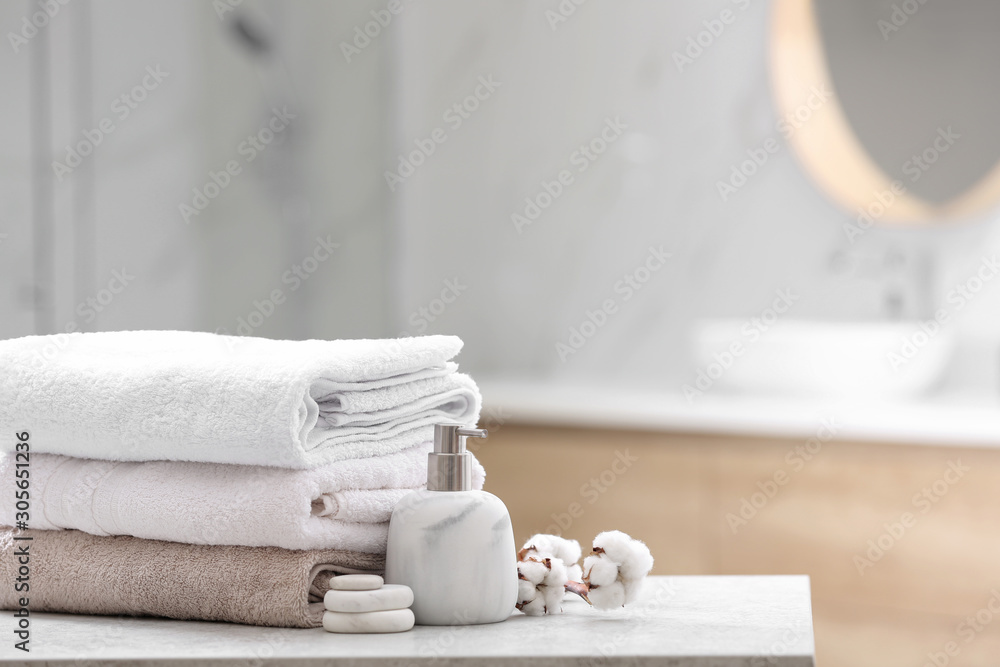 Fototapeta Clean towels, spa stones and soap dispenser on table in bathroom. Space for text