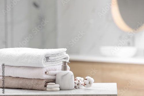 obraz lub plakat Clean towels, spa stones and soap dispenser on table in bathroom. Space for text