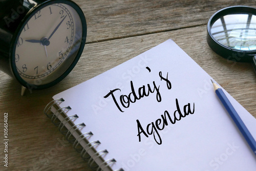 Photo Table clock,magnifying glass,pencil and notebook written with Today's Agenda on wooden background