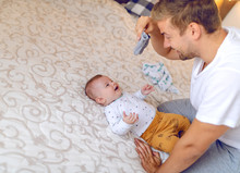Happy Handsome Caucasian Young Dad Holding Tiny Baby Socks And Preparing To Change Clothes To His Laughing Cute 6 Months Old Son. Bedroom Interior.