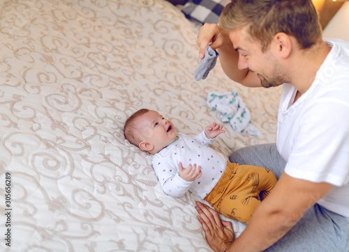 Happy handsome caucasian young dad holding tiny baby socks and preparing to change clothes to his laughing cute 6 months old son Canvas Print