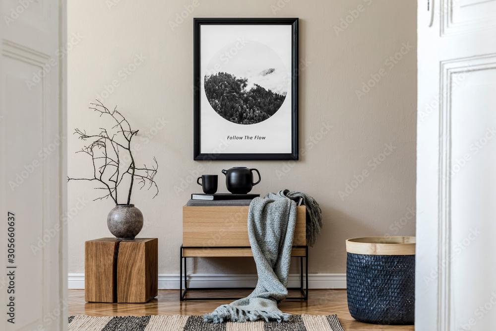 Fototapeta Modern scandinavian living room interior with black mock up poster frame, design commode,  leaf in vase, black rattan basket, books and elegant accessories. Template. Stylish home decor.