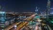 Aerial view of Financial center road day to night transition timelapse with shopping mall and under construction building with cranes from downtown, Dubai Creek harbor on background
