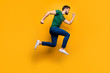 Full length profile side photo of serious focused guy jump run fast want buy spring black friday discounts wear casual style outfit isolated over yellow color background