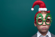 Portrait Of Serious Little Boy Wearing Headband With Santa Claus Hat Posing On Green Wall.