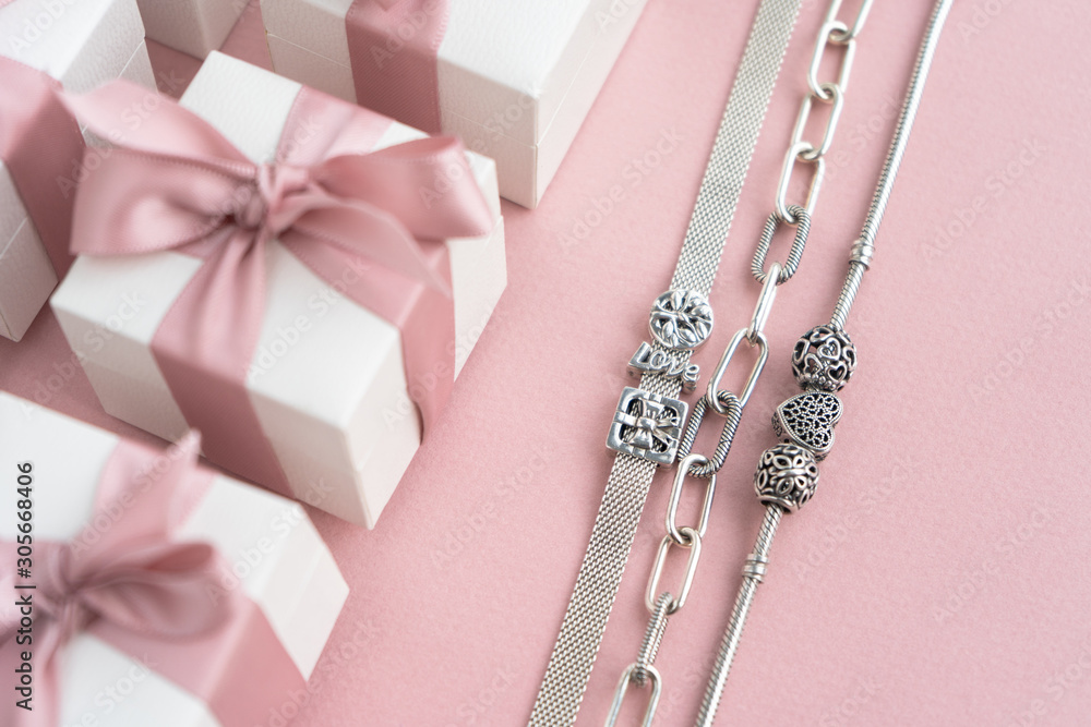 Fototapeta Gift boxes wiyh powdery ribbon. Powdery background. Silver bracelet with charms. Gift box for the New Year and Christmas. Best gift for Valentines Day and Mothers day.