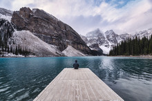 Traveler Sitting On Wooden Pier With Rocky Mountain In Moraine Lake At Banff National Park