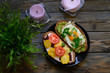 breakfast and brunch. two sandwiches of black bread, with cheese and vegetable filling, lie in a black plate, next to a lilac candles and a green plant on a wooden background