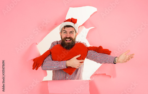 Smiling Santa man with heart shaped pillow looks through hole Wallpaper Mural