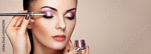 Obraz Makeup artist applies eye shadow. Beautiful woman face. Perfect makeup. Makeup detail. Beauty girl with perfect skin. Nails and manicure - fototapety do salonu