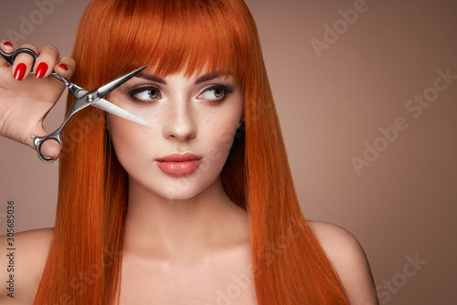 Photo Beautiful young woman with a bright makeup and a smooth long hair holds metal scissors