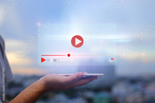 Obraz live video content online streaming marketing concept.Hands holding mobile phone on blurred urban city as background - fototapety do salonu