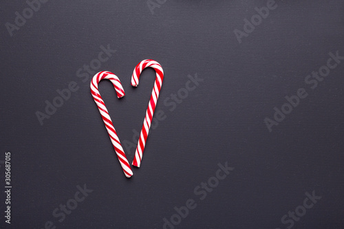 Two candy canes in shape of heart on black wooden background. Christmas, winter, new year concept - Image
