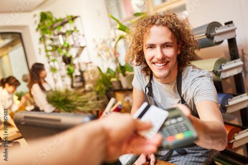 Fotomural Kunde zahlt mit Kreditkarte bargeldlos beim Kassierer