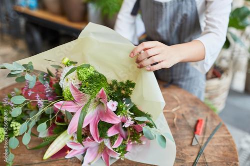 Florist beim Einwickeln von Blumenstrauß in Papier