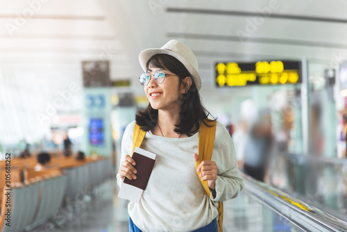 Canvas Print Happy Asian woman wear glasses, hat with yellow backpack is holding flying ticket, passport while waiting for the flight at the hall of airport