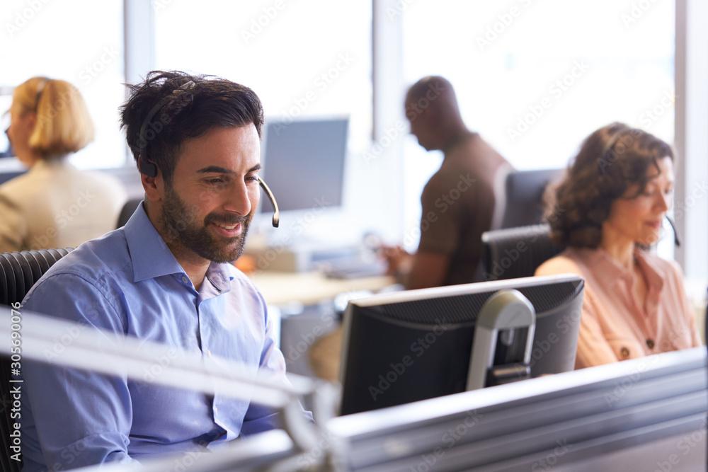 Fototapeta Businessman Wearing Telephone Headset Talking To Caller In Customer Services Department