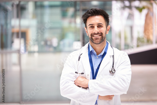 Fototapeta Portrait Of Male Doctor With Stethoscope Wearing White Coat Standing In Modern Hospital Building obraz