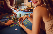 Chips In The Hands Of A Female Roulette Player In Casino Background.