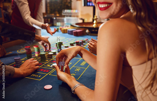 Chips in the hands of a female roulette player in casino background Obraz na płótnie