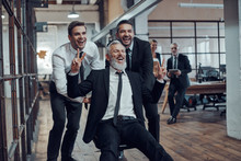 Cheerful Businessmen Pushing Their Boss On The Office Chair While Running In The Hallway