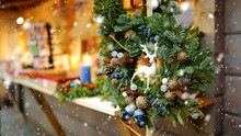 Beautiful Fir Tree Wreath As A Decoration Of A Wooden Market Stall On Christmas Market In Riga, Latvia. Decorated Shopping Stands With Variety Of Xmas Toys.