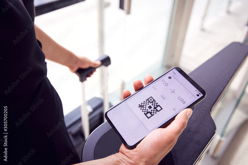 Fototapeta Close Up Of Male Passenger In Airport Looking At Digital Boarding Pass On Smart Phone