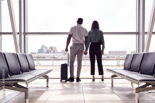 Rear View Of Business Couple With Luggage Standing By Window In Airport Departur Canvas Print