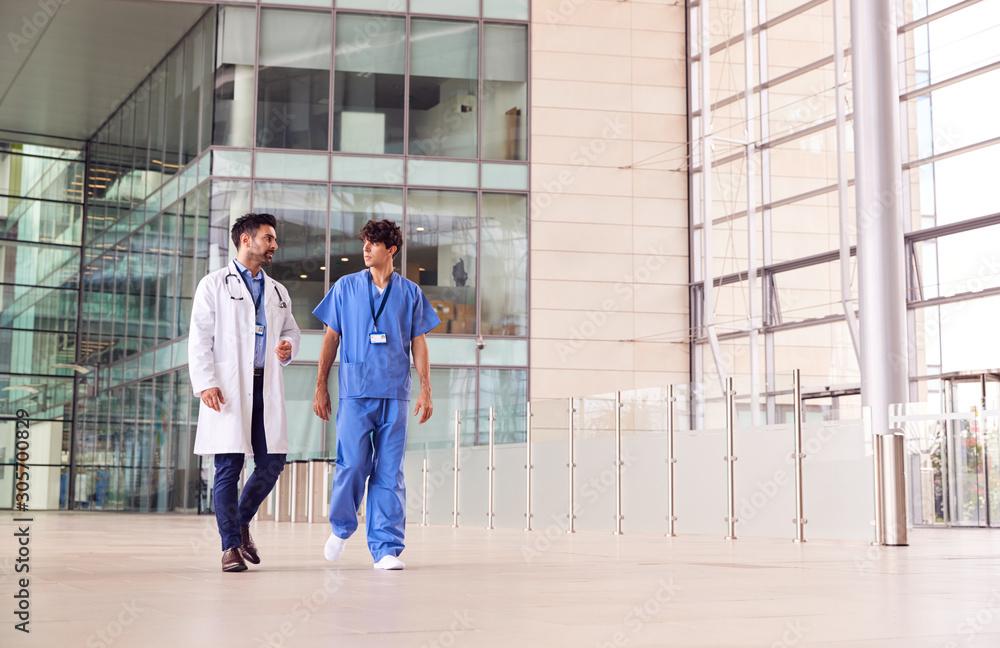 Fototapeta Male Medical Staff Talking As They Walk Through Lobby Of Modern Hospital Building