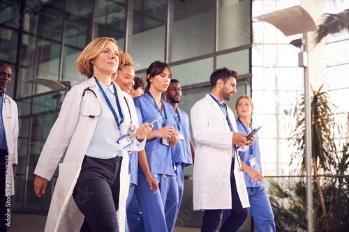 Fotomural  Medical Team Walking Through Lobby Of Modern Hospital Building