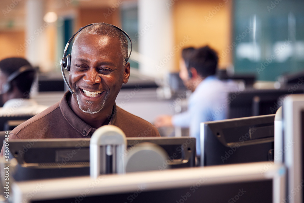 Fototapeta Mature Businessman Wearing Telephone Headset Talking To Caller In Customer Services Department