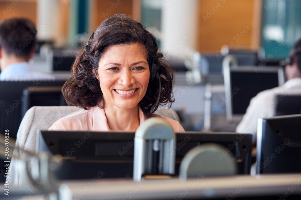 Fototapeta Mature Businesswoman Wearing Telephone Headset Talking To Caller In Customer Services Department
