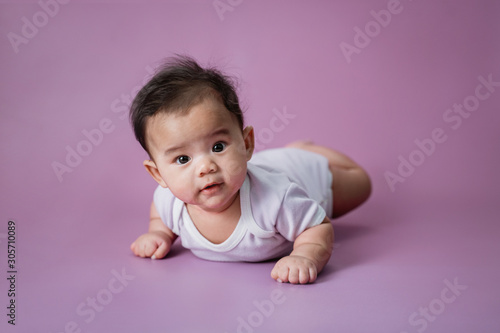 Obraz cute baby laying on her belly looking at camera - fototapety do salonu