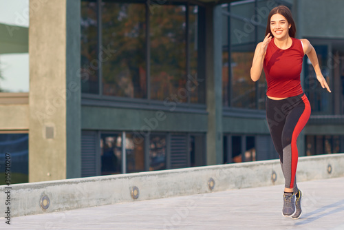 Fotomural Young woman exercising / running in urban park.