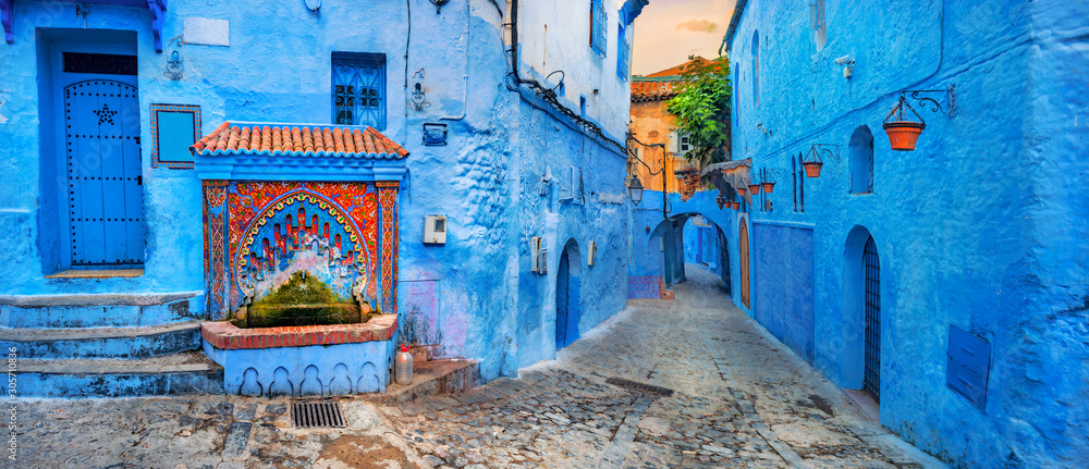 Fototapeta Fountain with drinking water on house coloured wall in blue town Chefchaouen. Morocco, North Africa