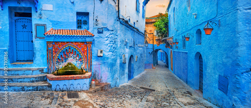 Fototapeta Fountain with drinking water on house coloured wall in blue town Chefchaouen. Morocco, North Africa obraz