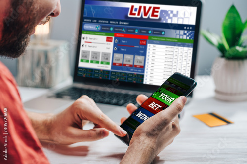 Fotografie, Obraz  Guy being happy winning a bet in online sport gambling application on his mobile