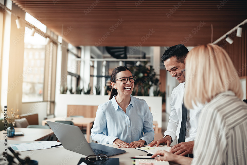 Fototapety, obrazy: Businesspeople laughing while working at an office table
