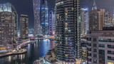 Fototapeta Nowy York - Aerial view of Dubai Marina residential and office skyscrapers with waterfront night timelapse