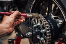 Motorcycle Maintenance, Lubricating Chain, Close-up.