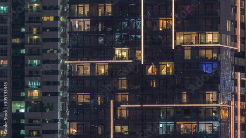 Photo Rows of glowing windows with people in apartment building at night
