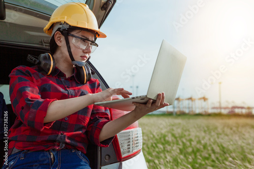Fotografia, Obraz Young female engineer in protective work white wear working with notebook in wind turbines, background wind turbines, wind turbines, clean energy engineer worker concept
