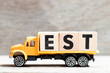 Truck hold letter block in word est (abbreviation of established, estimated, eastern time zone, expressed sequence tag) on wood background