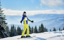 Portrait Horizontal Shot Of Happy Woman Skier Standing On Skis On Top And Turned Back To Camera. Reflection In Goggles In Sunny Winter Day. Concept Of Active Outdoor Recreation At Resort. Copy Space.
