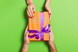 canvas print picture - Top view of giving and receiving a present on colorful background. A man and a woman holding gift in hands. Festive concept with copy space