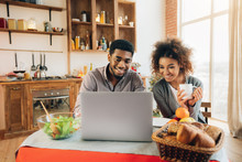 Happy African-american Couple Using Laptop At Kitchen
