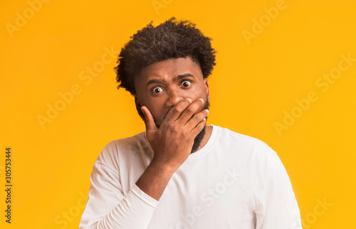 Amazed black man covering his mouth with palm Fototapet
